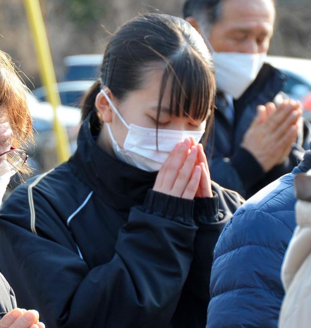 津波の犠牲になった母や妹2人、曽祖母を思って祈る、岡谷美海さん=2021年3月11日午後2時48分、岩手県大槌町の吉里吉里漁港