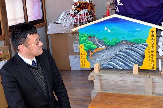 奉納した大きな絵馬を見る阪井健二さん=2021年3月9日、岩手県釜石市箱崎町の白浜神社