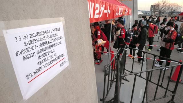 観客が集まるなか、試合当日に中止となった名古屋―ガ大阪。左は試合延期を伝える貼り紙