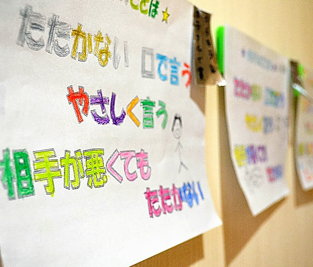 一時保護所の廊下の壁には、子どもたちが色をぬった「魔法の言葉」が貼られている。家に帰るときに希望して持って帰る子どももいるという=山形市