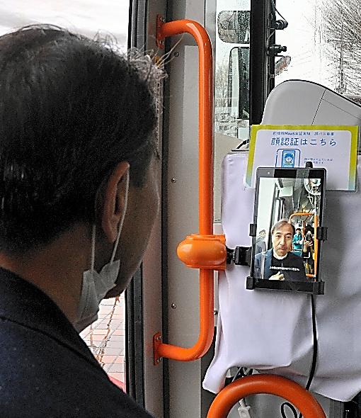 自動運転バスの実証実験に導入されたポラリファイの「顔パス決済」を試す社長の和田友宏氏=前橋市