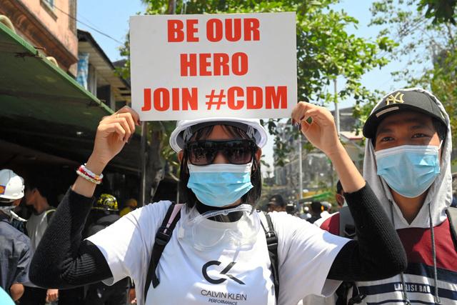 ヤンゴンで3月8日、クーデターに抗議して職場を放棄する「不服従運動」への参加を呼びかけるプラカードを掲げる女性=AFP時事