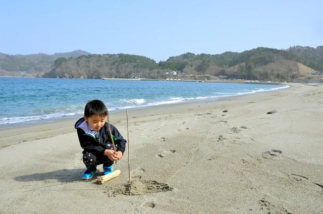 一般開放された根浜海岸で砂遊びをする子ども=2021年3月31日、岩手県釜石市