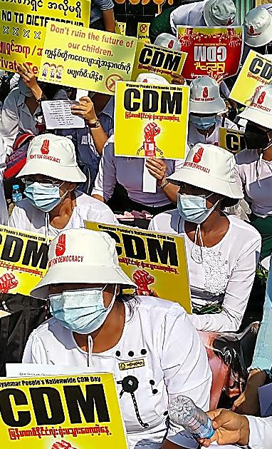 ヤンゴンで2月22日、プラカードを掲げる人々