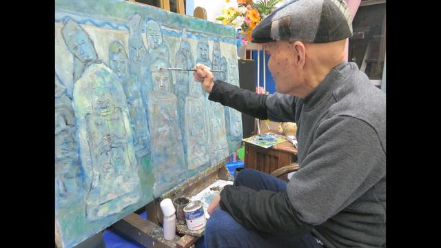 アトリエで石仏を描く清志初男さん=2018年3月、岡山県瀬戸内市、宮崎賢さん提供
