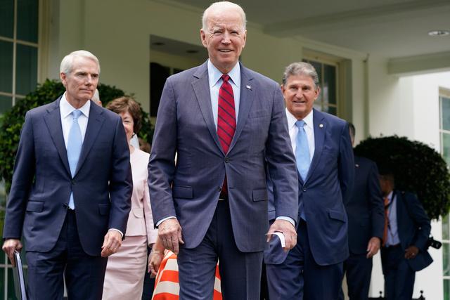 超党派の上院議員らと共に、報道陣の取材に臨むバイデン米大統領=AP