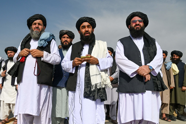 アフガニスタンの首都カブールの空港で8月31日、米軍の撤退後、メディアに向けて語るタリバンの報道担当のムジャヒド幹部(中央)=AFP時事