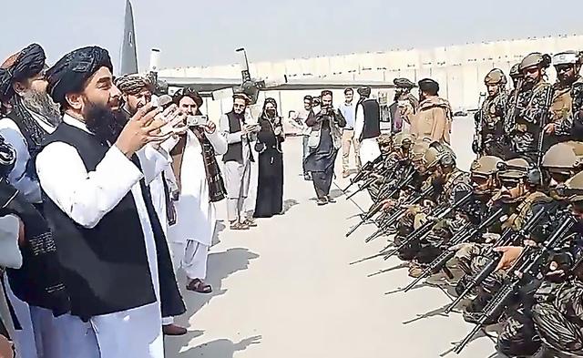 アフガニスタンの首都カブールの空港で8月31日、特殊部隊の隊員に話しかけるイスラム主義勢力タリバンの報道担当ムジャヒド幹部。タリバン提供=ロイター