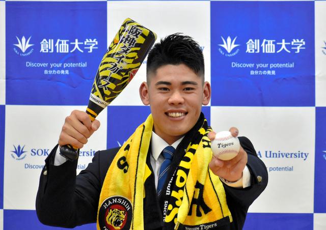 阪神のグッズを身にまとって喜ぶ、2位指名を受けた創価大の鈴木勇斗投手=2021年10月、東京都八王子市、加藤秀彬撮影