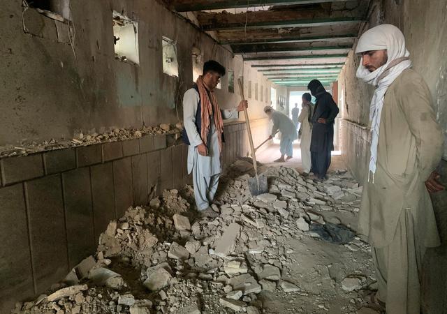 アフガニスタン南部カンダハルのモスクで15日、爆発があり、モスク内を調べる人々=AP