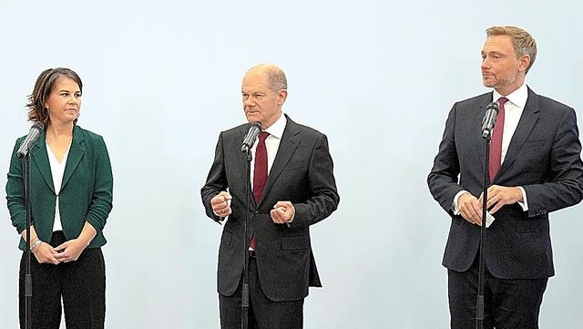 記者会見に臨む社会民主党のショルツ首相候補(中央)、緑の党のベアボック共同党首(左)、自由民主党のリントナー党首=AP