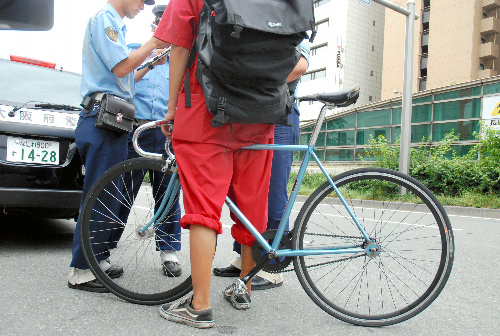写真:大阪府警の警察官にブレーキを取り付けるよう指導される「ピスト」の利用者=7月28日、大阪市中央区、長野佑介写す