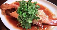 43)岡山のパクチー:蒸した魚にパクチーが入ったソースをかけ、生のパクチーをふんだんに使った料理。赤と緑のコントラストと、やさしい香りが食欲をそそる=堺市