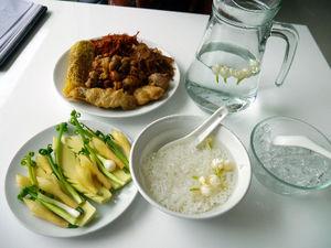 :ジャスミンの花で香りづけした水と氷をご飯に注いだ、冷たいおかゆ料理「カオチェー」。付け合わせと一緒に頂く