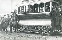 京都電気鉄道の1号車を前にした記念写真=1895年ごろ撮影。車両はブリル21E形台車をつけたダブルルーフのオープンデッキ。左の人物の法被には「京都電気鉄道 作事方」の文字があり、関係者とみられる