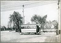 平安神宮近くを走る京都電気鉄道(京電)の電車。右後ろに平安神宮の建物が見える=1895年ごろ撮影。前部デッキに先走り(告知人)の少年が乗っている。電車後方は琵琶湖疏水。第4回内国勧業博覧会の会場が更地