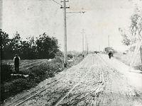 未舗装の竹田街道に敷かれた京電伏見線のレール=1900(明治33)年ごろ撮影。単線の狭軌が走る。1908年に複線化されているので、それ以前の撮影。当時は鴨川の勧進橋以南、竹田までは人家がほとんどなかっ