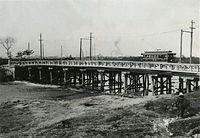 鴨川にかかる勧進橋を渡る電車=明治後期撮影。ダブルルーフとオープンデッキの古典的スタイルの木造電車。当時は木橋上を併用軌道で渡っていた