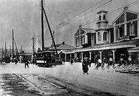 初代京都駅と、京都電気鉄道(京電)の電車。京都駅舎2階には、1904(明治37)年に駅構内に開業した洋食店の看板が掲げられる=1910年ごろ撮影。京電開業当初は集電装置がトロリーポール1本だったが、写