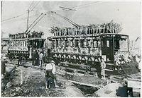 京都市電開業を記念し、「運輸開始」と書かれた飾り付けをした電車。建設工事中の壬生車庫を出発する=1912(明治45)年撮影。日本最初の路面電車を開業した京都電気鉄道(京電)に対抗し、京都市も中心部で路