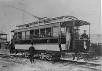 京都市電開業当時の17号車=1912年、壬生車庫内。制服姿の若者が乗車している