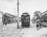 まもなく廃止される京都市電木屋町線の木屋町御池停留所に停まる狭軌のN125号車=1926(大正15)年撮影。12号系統の京都駅前発電車に、蜘蛛の巣模様の羽織を着た女性が乗り込む。京都市電に買収された京