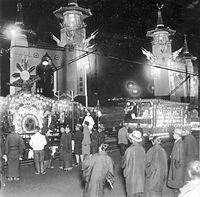 昭和天皇の即位の礼前夜、記念する京都市電の花電車が七条奉迎門前を通過する=1928年撮影。雅楽の楽器「鼉太鼓」(だだいこ)がデザインされた豪華な装飾の電車(左)も走る