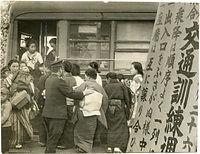 交通マナー訓練の1日目、乗降する乗客=1940(昭和15)年撮影、四条烏丸停留所。「乗降は順序よく一列に」、「出入口をふさがぬ様」、「座席は互に譲り合ひ」と書かれた看板がみえる