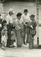 河原町線の河原町三条停留所で乗車券を買う乗客=1946(昭和21)年撮影。京都市電気局(47年に京都市交通局と改称)は混雑緩和のため、戦時中の45年4月15日から車内での乗車券、回数券の販売を中止して