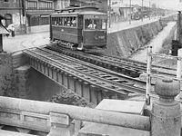 明治の面影を残す堀川線(北野線)のN127号車が撮影名所の堀川中立売の鉄橋を渡る=1954(昭和29)年撮影。手前は中立売通の中立売橋。開業当時は橋の東詰に転車台を設け、向きを変えていたが、事故が多発