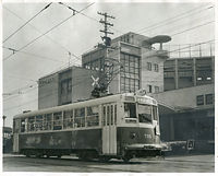 京都市交通局前の京都市電千本線を走る最新型の700型電車705号車=1958年撮影。軽量化車体で両開き式の4枚折り戸の自動ドアが特徴。後方は壬生車庫に併設された京都市交通局庁舎(当時)