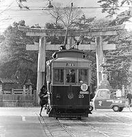 北野天満宮の鳥居を背に、京都市電堀川線(北野線)の北野停留所で発車を待つ25号車=1961年撮影。北野から京都駅前までを結ぶ路線が、7月に全線廃止された。堀川線は、1895(明治28)年に日本最初の路