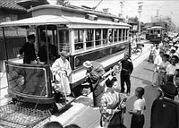 1961年7月31日限りで廃止される京都市電堀川線(北野線)で、ベスチビュール(前面窓)を取り外して創業時のスタイルに復元した電車を使った撮影会が開かれ、明治の服装をした乗客らが乗り込んだ=1961年