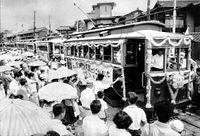 1961年7月31日限りで京都市電堀川線(北野線)が廃止された。終点の北野で開かれたお別れの会にはモールで飾られた電車が並び、別れを惜しむ市民が集まった=1961年7月31日撮影