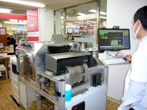 写真:ブックマシンは1階の奥に置かれている。プリンターと製本機を組み合わせた機械だ=東京都千代田区の三省堂書店