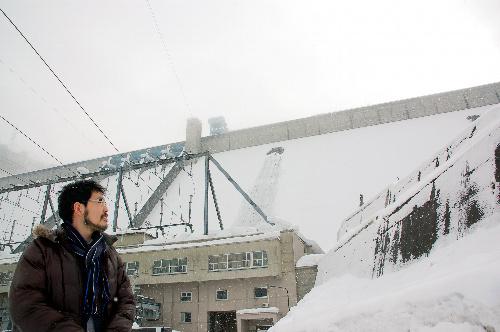 写真:コンクリートの巨大な壁、田子倉ダム(奥)を見上げる開沼博さん。頂上部分は、舞う雪にかすんでいた=2月29日、福島県只見町