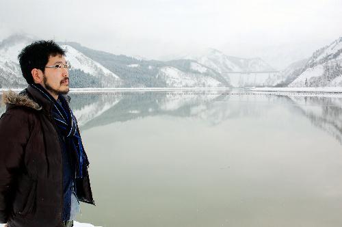 写真:静寂に包まれた只見ダムに立つ開沼博さん。小雪の向こう、遠く上流側に田子倉ダムも見えた(右奥)=2月29日、福島県只見町