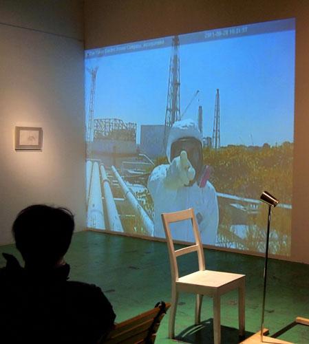 写真:竹内公太展「公然の秘密」の会場。指さし作業員の映像の前の椅子に座ると、竹内と糸電話で話すことができる