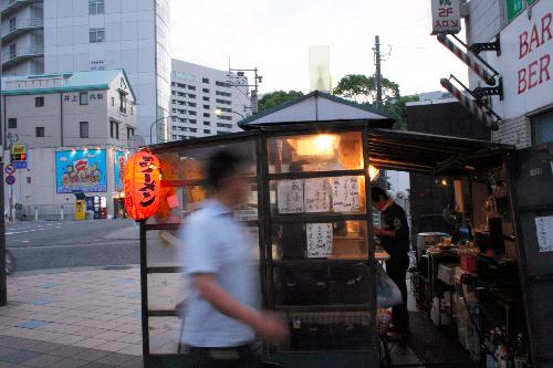 写真:夕暮れ時、福岡市庁舎(奥の中央)の近くで店を構える屋台=福岡市中央区