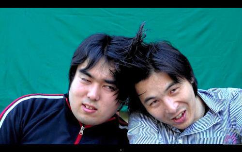 写真:スプレーで2人の髪をくっつけたMEGWIN(右)。左はスタッフ=MEGWINの動画から