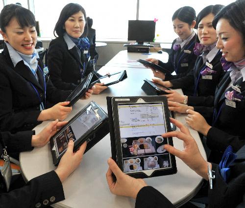 写真:iPadを手にミーティングをする全日空の客室乗務員=羽田空港、遠藤真梨撮影