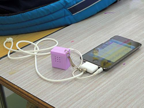 写真:写真2:本村君が使っているiPod Touch。コネクターに接続されているのは、音を周囲に出すためのスピーカー。機器は学校へ支給されたものを借りる形で利用している(撮影:西田宗千佳)