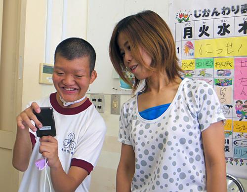 写真:写真1:沖縄県糸満市・西崎特別支援学校に通う本村信太郎君と、2年5組副担任の当銘成美教諭。iPod Touchとアプリの力で、コミュニケーションの幅はぐっと広がった(撮影:西田宗千佳)