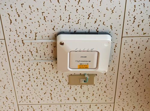 写真:写真5:廊下に設置された無線LANアクセスポイント。一般的な市販品で、特別なものではない。これが校内に設置され、どこでもネットが使えるようになっている(撮影:西田宗千佳)