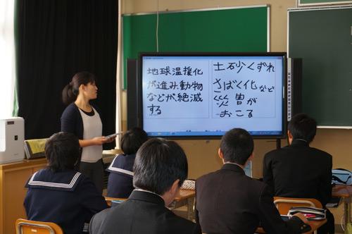写真:写真2:社会科の授業中の風景。教壇の近くにインタラクティブ・ホワイトボードが、生徒の机にiPadがあるのが違い(撮影:西田宗千佳)