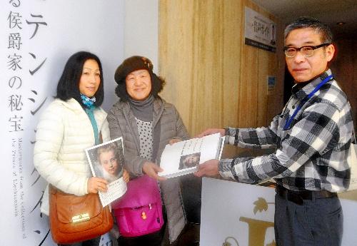 写真:西内副館長から図録を受け取る畠中さん(中央)と岡崎さん(左)=県立美術館