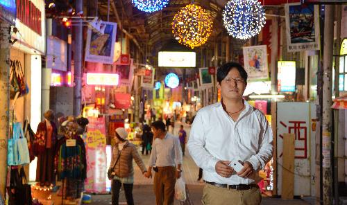 勤務先の土産物店がある国際通り沿いで携帯端末を手に立つ川上豊さん=那覇市、関口聡撮影
