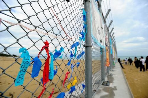 普天間飛行場の移設先候補である辺野古の海岸。米軍キャンプ・シュワブ(左側)との境のフェンスには「NO BASE」などと書かれたリボンが=沖縄県名護市、関口聡撮影