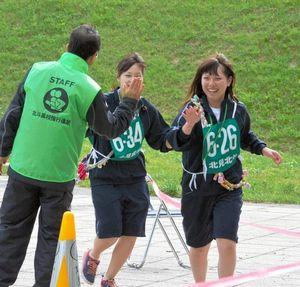 写真:ゴールで校長に出迎えられる生徒=北見市