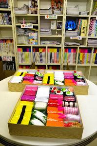 写真:「おむつ寿司」の松竹梅各セット。本棚には最近の「ワイヤーママ徳島版」が並ぶ=徳島市北沖洲1丁目